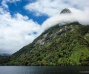 Ein Wolkengürtel um eine Bergspitze erinnert an einen Schal aus zuckerwatte Doubtful Sound Neuseeland