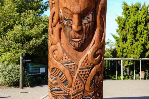 Ein mit Schnitzkunst versehener Stamm, Maorikunst im Buried Village in Rotorua auf der Nordinsel Neuseelands
