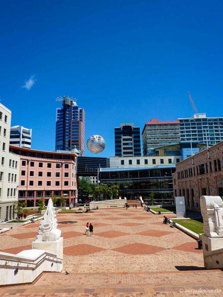 Platz vor dem Civic Center in Wellington mit in der Luft schwebender Stahlkugel, die aus 5 verschiedenen Farnsorten besteht