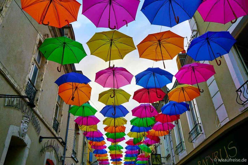 Viele bunte Regenschirme schirmen den Blick zum Himmel ab. Gefunden in einer Gasse in La Ferté-Bernard, Frankreich.