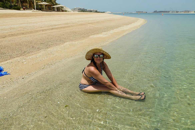 Urlaub am Strand genießen - Frau sitzt im Wasser weitere Informationen unter www.wiraufreise.de