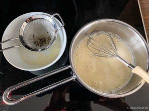 Den angerührten Pudding durch ein Sieb in die kochende Milch sieben.
