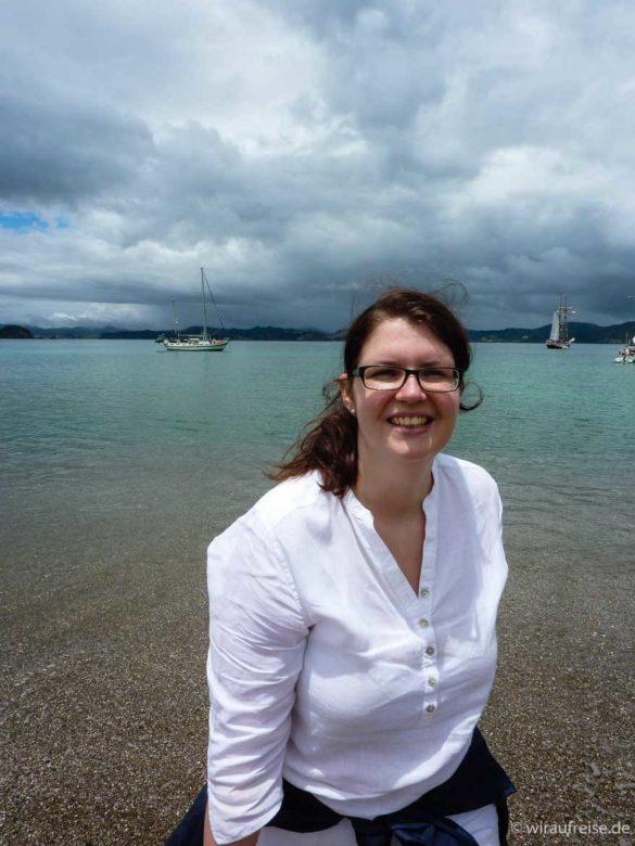 lachende Frau in weißer Bluse am Ufer - bay of islands neuseeland nordinsel