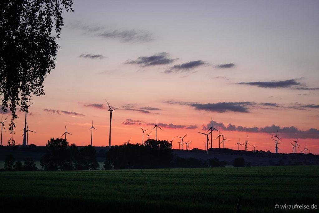 Sonnenaufgang in Wangenheim in Thüringen mit Windrädern am Horizont